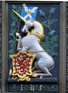 Scottish unicorn, flag and shield carved on wall at Edinburgh Castle.